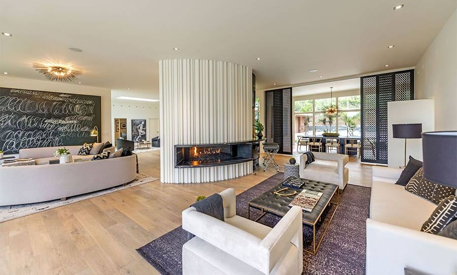 <p>The couple's living room has a number of different seating areas that are separated by a large pillar in the middle of the room with an open fireplace. Black sliding doors open out onto a separate dining room where there is seating for eight – perhaps they can host their friends George and Amal Clooney and their twins for dinner here!</p>