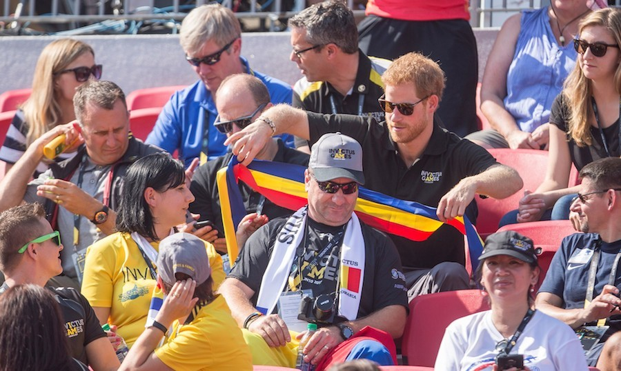 On the first official day of competition, Prince Harry headed up to York University to watch track and field events. Here, the royal helps a fan get ready to cheer on his country. 