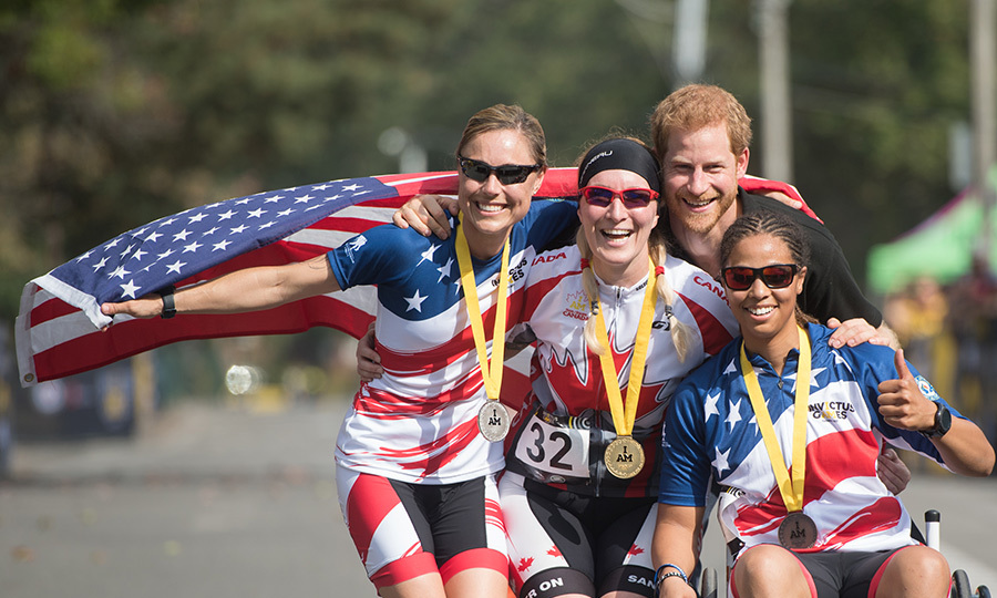 Prince Harry handed out medals and posed with the top three athletes in women's cycling. Quebec native Julie Marcotte (C) took home gold in the event. 