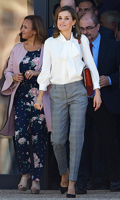 <p>Queen Letizia of Spain was all business in grey trousers, a pussy bow blouse and Zara handbag during a visit to a school in Teruel, Spain. </p>