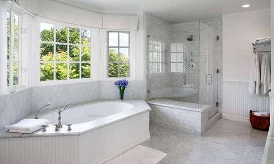 <p>There are eight bathrooms in James' new home, including this spacious suite that is fitted with white marble tiling, a large bathtub and separate glass enclosed shower cubicle. A large bay window keeps the room light and airy, and overlooks the home's sprawling private garden.</p>