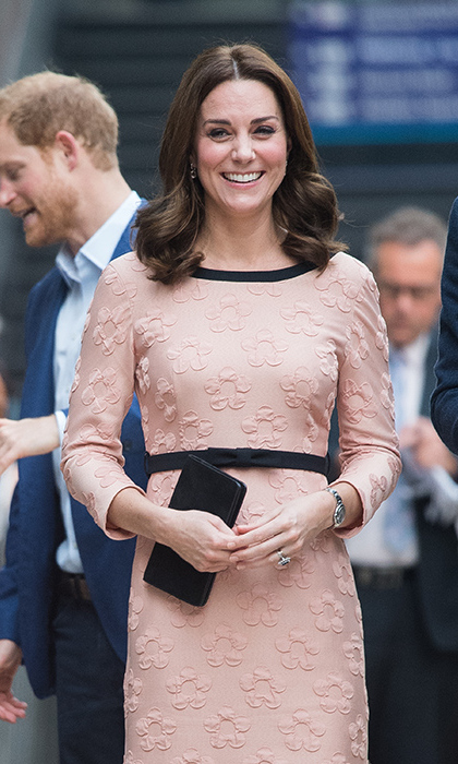 Kate showed off her tiny baby bump in a floral-patterned pink dress by Irish designer Orla Kiely. It also looks like she cut a few inches off her glossy tresses. 