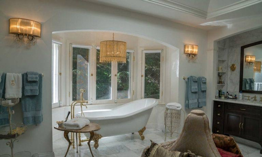 <p>Serena's home has seven bathrooms, including this master suite, which is decorated with tiled marble flooring and worktops, a wooden dresser and a cushioned seating area. Perhaps the highlight is this free-standing bathtub, which features gold feet and taps plus monogrammed towels featuring gold embroidered 'S' motifs.</p>