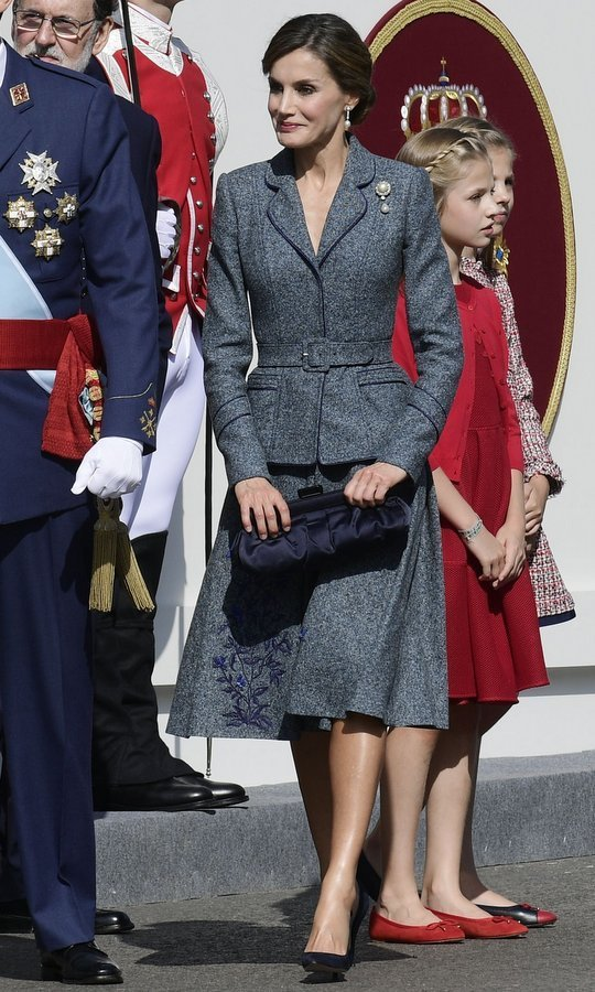<p>With daughters Princess Leonor and Princess Sofia standing behind her, Spain's Queen Letizia channeled 1950s New Look style in a tailored grey Felipe Varela skirt suit with peplum waist and embroidered hem for the National Day military parade in Madrid on October 12. King Felipe's wife accesorized the outfit with a dark blue satin handbag and pearl and diamond jewelry.<br /><br />Photo: JAVIER SORIANO/AFP/Getty Images</p>