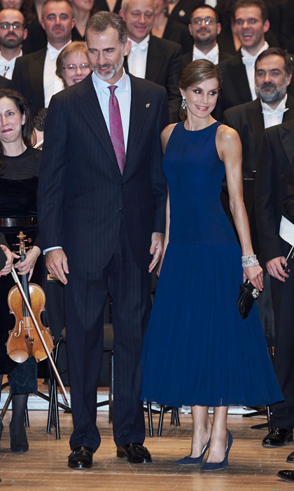 <p>The day before — Thursday, October 19 — Letizia attended the awards' XVI Musical Week closing orchestral concert with her husband. The mom-of-two sported a wrap around ponytail for the occasion. The chic, albeit simple updo highlighted the royal's Yanes blue topaz chandelier earrings.<br /><br />The Queen of Spain stunned at the musical event wearing a sleeveless royal blue dress that featured a flared pleated skirt by her go-to designer Felipe Varela. Letizia accessorized her ensemble with her black Tod's rhinestone toggle clutch and navy Nina Ricci suede pumps. <br /><br />Photo: Carlos R. Alvarez/WireImage</p>