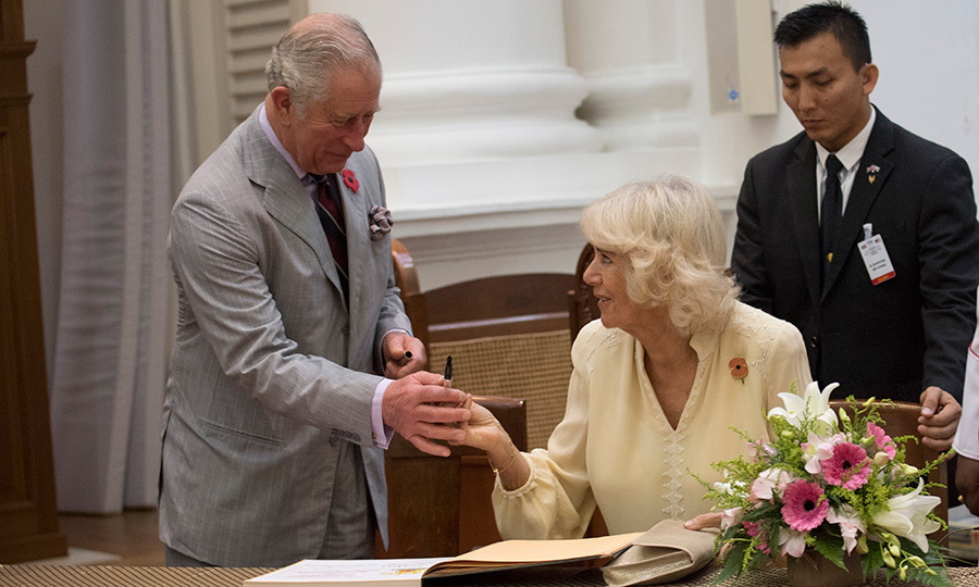 <p>Prince Charles handed his wife Camilla a pen to sign the guestbook at St George & Otilde's Church in Penang, Malaysia. The 19th century house of worship is the oldest purpose-built Anglican church in Southeast Asia.