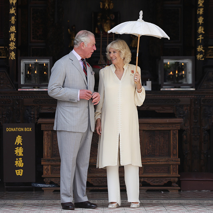 <p>The royal couple shared a smile outside the Han Jiang Temple in Penang. With temperatures in the upper '80s, Camilla was well equipped with her light tunic and parasol.