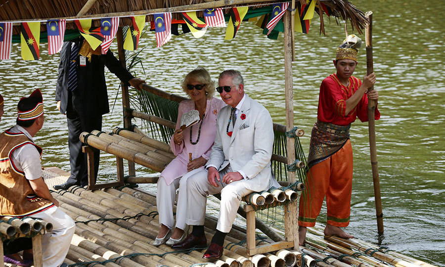 <p>Seated alongside her husband, Duchess Camilla kept cool with a fan and sunglasses as the royal couple took a ride across a lake on a traditional raft in Kuching, Sarawak, Malaysia. Charles, too, had it made in the shades in sunnies and his dapper white suit. 