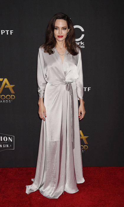 Angelina Jolie wore silver satin dress by Kate Middleton's favorite Jenny Packham to the Hollywood Film Awards on November 5. The <em>First They Killed My Father</em> director added a red lip and a full-bodies blowout to complete the look.