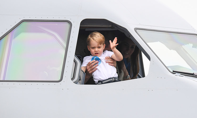 Prince George waving to photographers whilst visiting a helicopter.