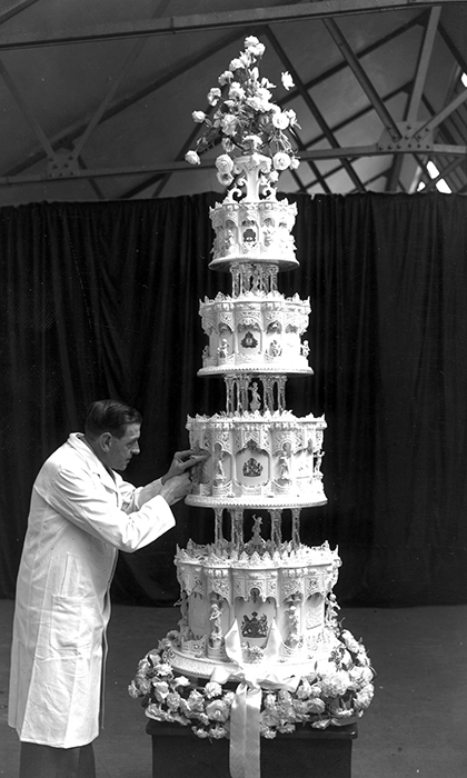 The wedding reception was held at Buckingham Palace where guests were presented with posies of white heather and myrtle as favors. The wedding cake was a grand affair, standing 9ft high, weighing 500lbs and featuring four tiers. Made from ingredients received from the Australian Girl Guides, the cake was cut using Philip's sword. One layer was kept until the christening of Prince Charles and another was sent back to Australia as a thank you.