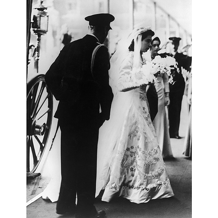 On her wedding day, wearing a beautifully embroidered dress by Norman Hartnell, Princess Elizabeth arrived at Westminster Abbey in the Irish State Coach with her father King George VI. Since her wedding occurred while Britain's austerity measures were still in place after WWII, Elizabeth famously saved up ration coupons to purchase the material needed to make her gown. 