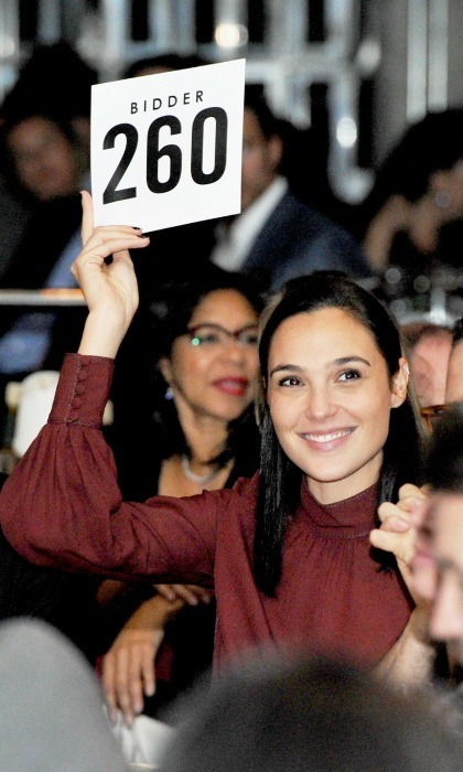 Bidder 260, also known as Gal Gadot, was among the starry crowd at the 2017 GO Campaign Gala in L.A. as well. The <em>Wonder Woman</em> actress put up a bid at the fundraiser, looking elegant in a red wine-colored blouse and big smile. 