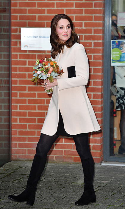 The Duchess looked particularly radiant and fresh in a white, knee-length coat by Goat. She wore the cover-up on a visit to Hornsey Road Children's centre in London on 14 November. She added a simple black clutch bag and on–trend long line boots by Stuart Weitzman. A bunch of blooms proved to be the perfect accessory!