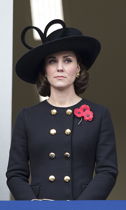 The Duchess of Cambridge looked stunning as she wore a strikingly bold, black classic double-breasted coat complete with statement gold buttons by British high-end designer Alexander McQueen, on Remembrance Sunday, 12 November. She teamed the military-inspired coat with a black fascinator and a red poppy.