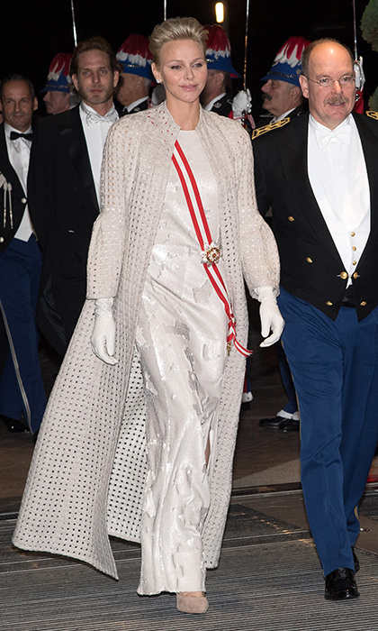 In the evening, Princess Charlene swapped her royal blue velvet for a sweeping, perforated coat by Akris worn over a gown by the brand. The royal finished off the look with white gloves and suede shoes in a natural hue. 