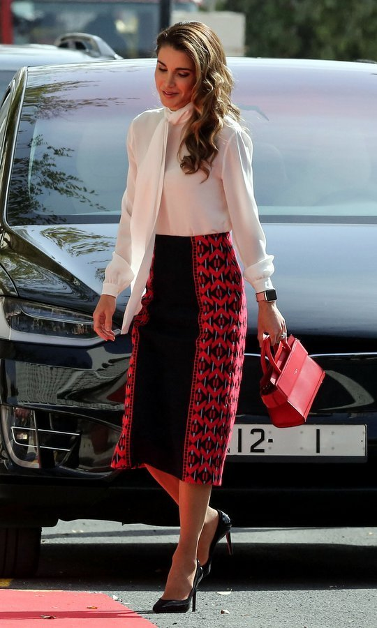 Here's a little officewear inspo from Queen Rania of Jordan! The monarch's wife attended the opening of parliament in Amman on November 12 wearing a red and black pencil skirt with a white pussy-bow blouse. The royal carried an on-trend mini bag – the Horizon Mini Leather Satchel by Givenchy – for the occasion.
