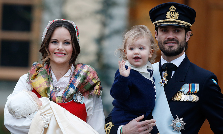 Here, the royal couple arrive. Princess Sofia has two-month-old Prince Gabriel in her arms while husband Prince Carl Philip totes 19-month-old Prince Alexander.