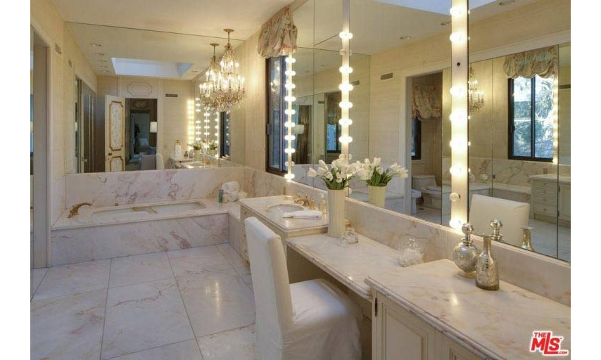 There are five-and-a-half bathrooms in the spacious home, including this suite which looks like the perfect spot for Victoria's Secret model Behati to pamper and get ready for her red carpet appearances. The bathroom is fitted with a luxurious marble suite and tiles with a dressing table area and Hollywood-style lights around the mirrors.