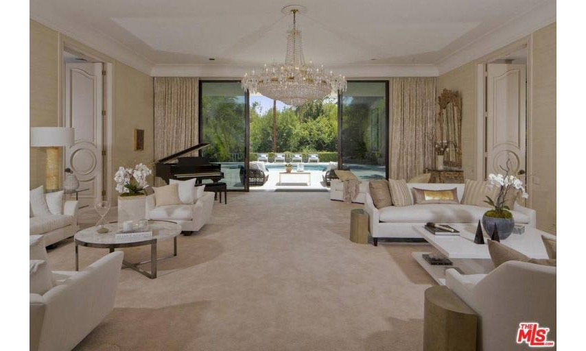 The home has an incredibly spacious living room area that leads straight through to the private terrace and swimming pool area. It is opulently furnished with two separate seating areas, an ornate chandelier hanging from the ceiling, and a grand piano where Adam can focus on writing new music.