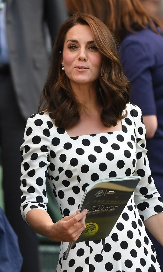<p>Long, curly and with a middle parting the Duchess of Cambridge is seen here at the Wimbledon Tennis Championships in July. Her long floaty curls looked striking against her white summer dress, making her hair look in tip top condition.</p>