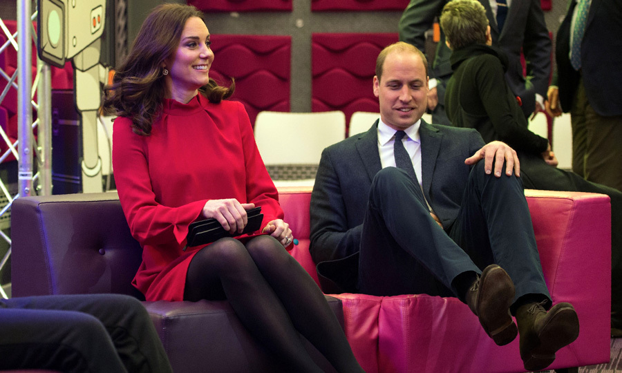 Put your feet up! Prince William hilariously lost his balance as he and Kate Middleton listened to a presentation at MediaCityUK. The Prince and Kate, who wore a berry tunic dress by GOAT, also spoke to young children during the event on December 6.