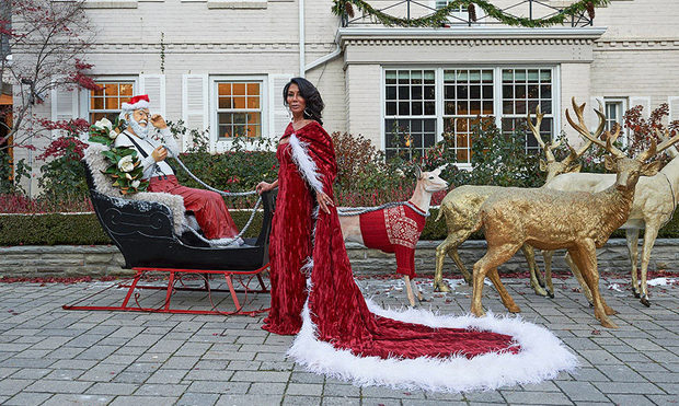 Ann Kaplan Mulholland in a red dress and cape next to a Christmas installation of Santa in his sled with reindeer.