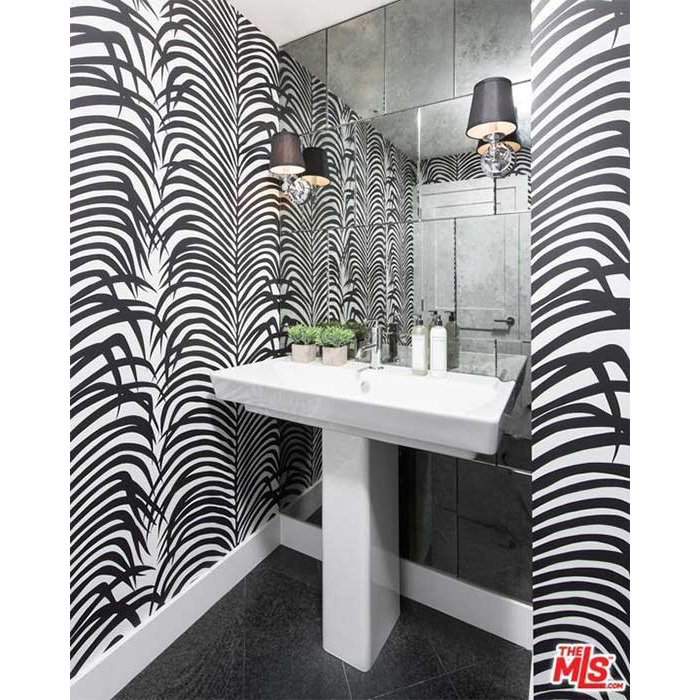 <p>Another of the smaller bathrooms in Kendall's apartment has a unique monochrome design with black and white patterned wallpaper and a white fitted suite and black tiled flooring. This small bathroom leads onto the living room area, while there is a further en suite bathroom on Kendall's guest bedroom.</p>