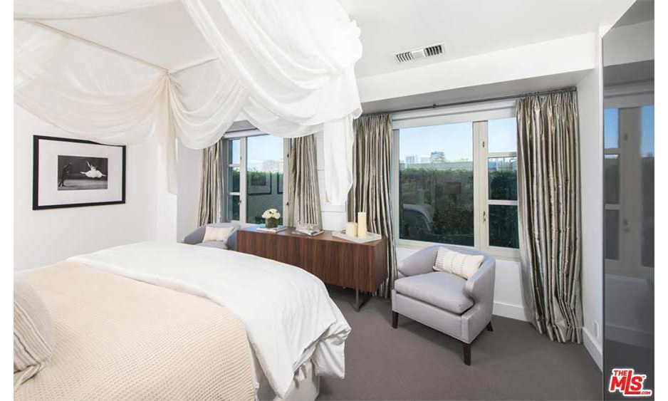 <p>Kendall's apartment has two bedrooms including this suite which has double windows and great views out onto the LA neighbourhood of Westwood. The bedroom is decorated in a similar white and grey colour scheme to the rest of the home, and has a double bed with draped curtains hanging around the outside.</p>