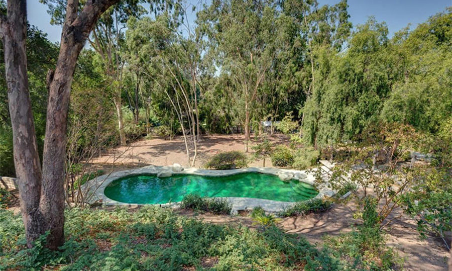 <p>A swimming pool with rustic boulders is located within the garden and looks almost lagoon-like. The grounds are park-like, with numerous trees and hedges, a contrast from the manicured lawns and pristine terraces seen in many other celebrity homes.</p><p>Photos courtesy of Trulia</p>