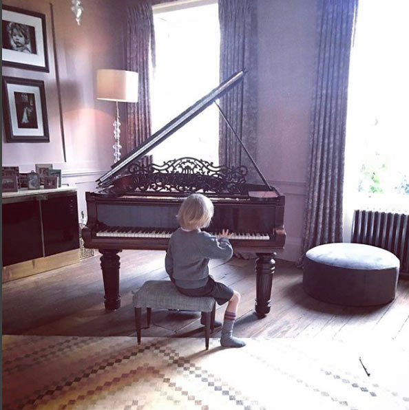 <p>A piano sits within one of the family rooms on the ground floor, the perfect place for the children to practice their musical skills, and in Buddy's case – learn how to play <em>Mary had a little lamb</em>. This room has traditional wooden flooring with a patterned rug, and floor-length patterned curtains at each of the large windows.</p>