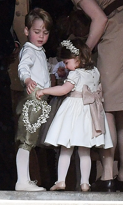 Prince George gave his litter sister Princess Charlotte a hand with her bridesmaid duties at their aunt Pippa's wedding in May. 