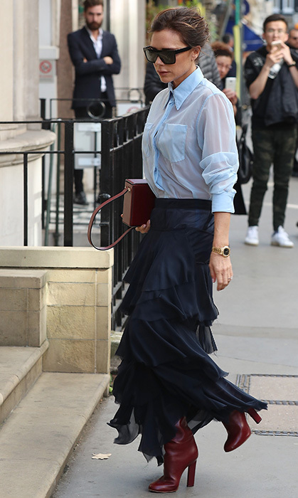 <p>Victoria loves a skirt and blouse pairing and she pulls it off perfectly in this photo. We adore her black, frilled skirt with sheer, blue blouse and funky, brown leather boots. The star wore the outfit for a visit to her Dover Street store in London in September.</p>