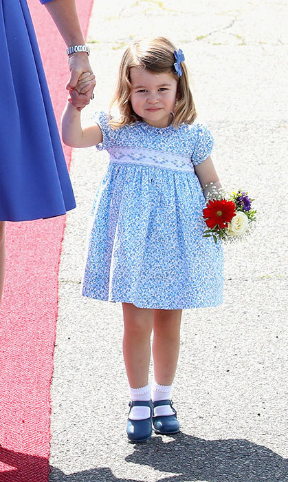 <p>Princess Charlotte wore another pretty floral dress for her family's tour of Berlin in July. The little girl looked lovely in the blue frock with matching shoes and hair bow. Her small bouquet of flowers finished off her look perfectly.</p>