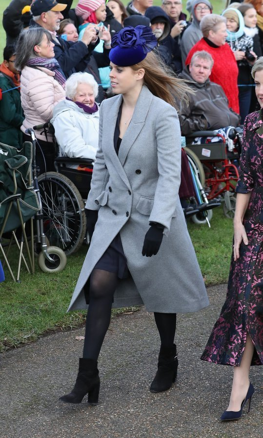 For Christmas with the Queen at Sandringham on Dec 25, Princess Beatrice wore a grey double breasted coat with ruffled details over a dark dress. The Queen's granddaughter accessorized with black booties and gloves, and a bright blue floral-motif hat.