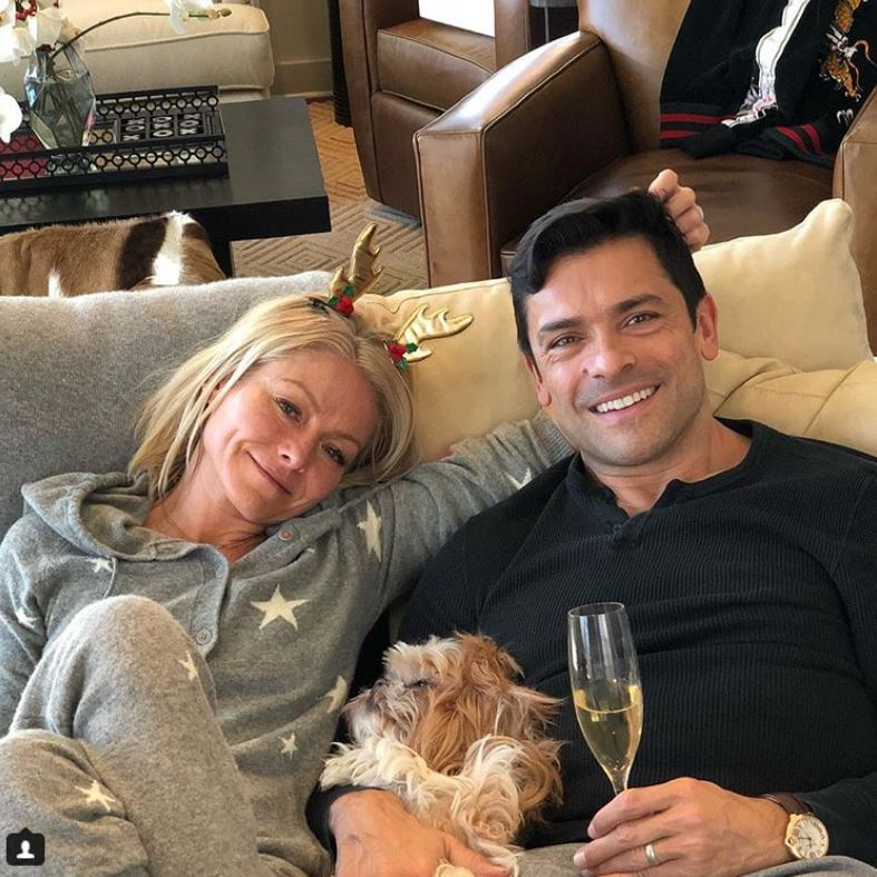 "Kelly Ripa and Mark Consuelos took a moment for themselves and their dog Chewie on Christmas morning. The Riverdale actor wrote alongside the cozy photo: ""Feliz navidad from the Consuelos fam and Chewie. #antlers.""