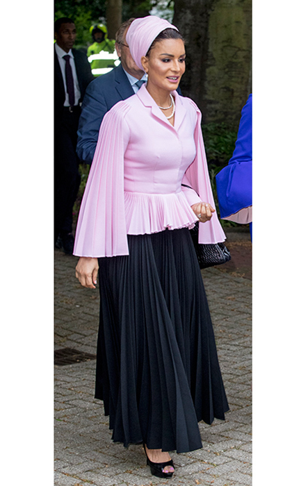 Couture queen and Qatar royal Sheikha Mozah bint Nasser wore this pleated pink look to join Queen Maxima at the The Hague in May 2017. The pink peplum top with cape detail and black pleated skirt are by Christian Dior haute couture.