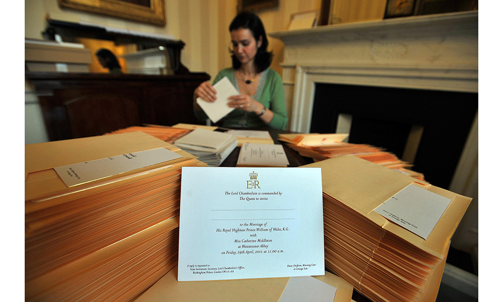 A member of the Lord Chamberlain's Office (name not given) inserts Prince William and Kate Middleton's wedding invitations into envelopes at Buckingham Palace, on February 16, 2011 in London, England.
