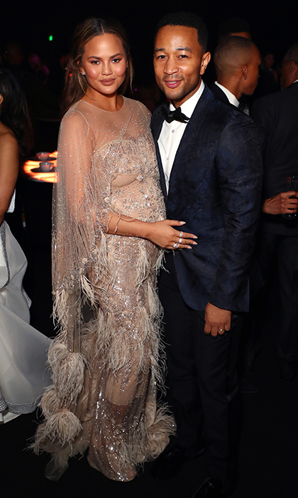 The man of the hour! John Legend, who was the creative force behind the 11th annual Art of Elysium HEAVEN gala, posed with pregnant wife Chrissy Teigen at the event on Golden Globes weekend. Chrissy looked stunning in a golden gown festooned with a feathery fringe.