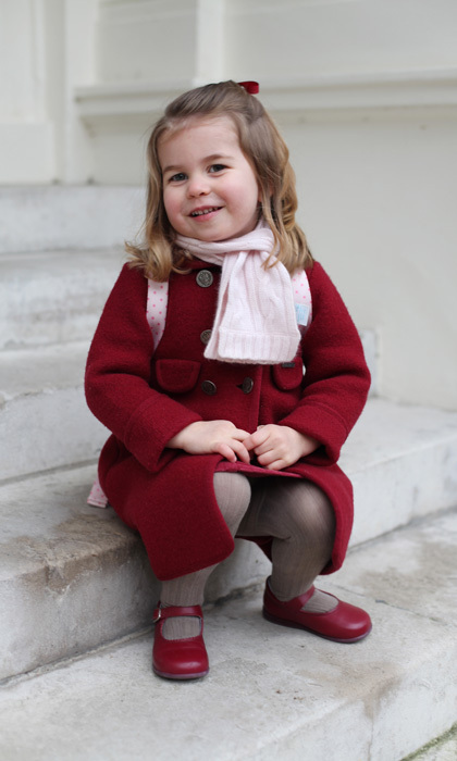 Proud mom Kate marked Princess Charlotte's first day of nursery school with a pair of adorable new portraits in which the youngster posed in a red coat with matching shoes and a pink cashmere scarf by fellow royal Marie-Chantal's kids line.