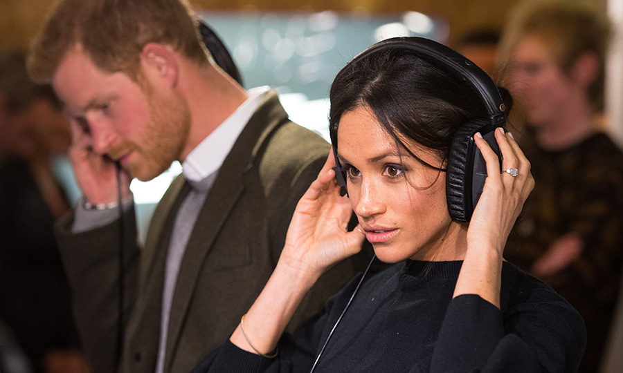 Prince Harry and Meghan Markle listened intently to a broadcast through headphones at Reprezent 107.3FM, where they also spoke with young DJs involved in the station's youth programme.