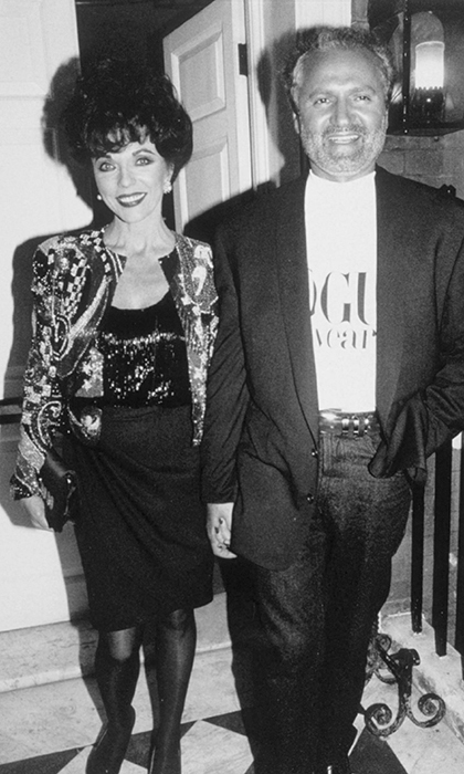 Joan Collins held hands with the gregarious designer at a <em>Vogue</em> party in London in 1991. 