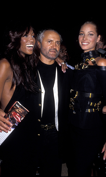 "Naomi Campbell and Christy Turlington, rocking a Versace bondage look, flanked founder Gianni in 1992. The designer is widely recognized as a catalyst for the explosive rise of the supermodels when he had Naomi, Christy, Linda Evangelista and Cindy Crawford sing along to George Michael's ""Freedom"" in 1991 after all starring in the music video.  