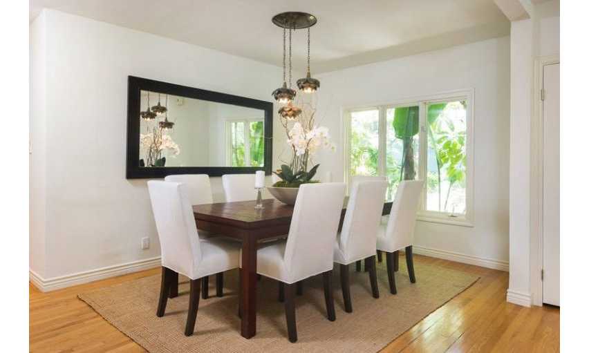 <p>The dining room area is situated at the end of the family room and features a wooden dining table with seating for up to six guests. A statement light fitting hangs over the centre of the table, where light also floods in through a large window.</p>