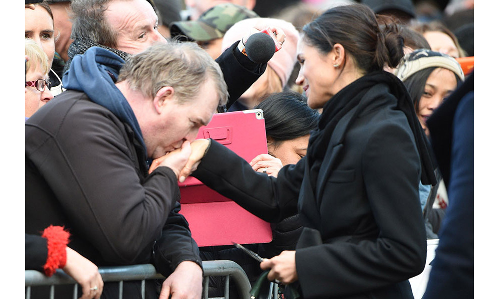 <p>One enthusiastic royal fan kissed Meghan's hand as she greeted the crowds outside Cardiff castle on Thursday afternoon. </p>