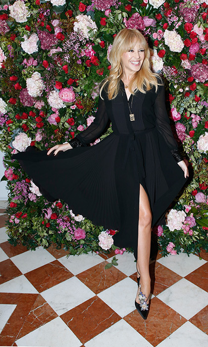 Kylie Minogue showed off her megawatt smile as she twirled around for the camera in Roger Vivier shoes that cost more than $3,000! Posing against a gorgeous floral backdrop, the singer showed off her elegant ensemble as she hopped from show to show during Paris Couture week.