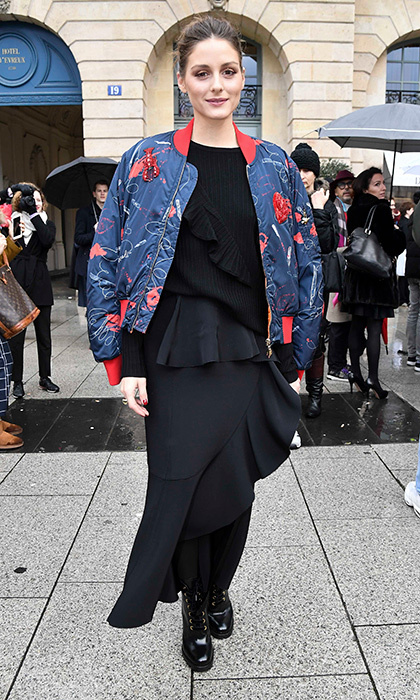 Ever the fashion maven, Olivia Palermo looked super cool in a black dress, embroidered bomber jacket and slick booties to attend the Schiaparelli show. 