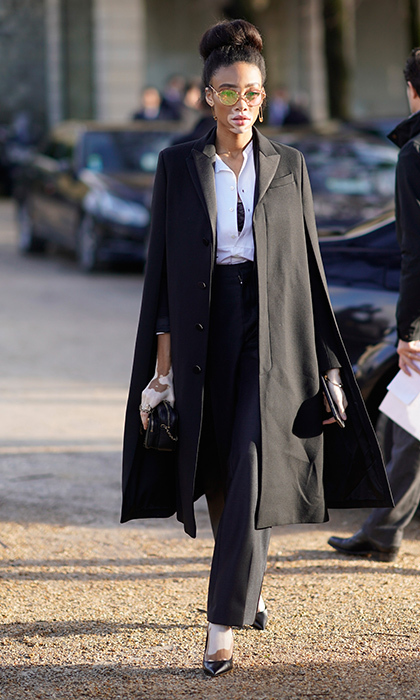 Supermodel Winnie Harlow looked cool as ever in black trousers, a white blouse and a matching black caped trench. Sealing the fashion deal with a slick pair of shades, this model was ready for the runway.