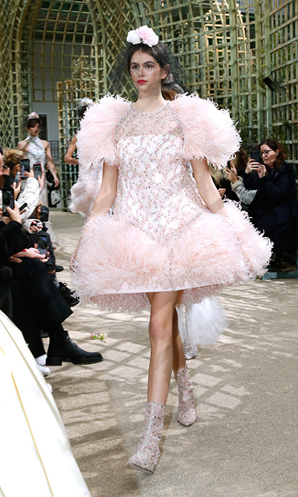 Kaia Gerber made her Haute Couture debut at Paris Fashion Week with the iconic Chanel. The budding supermodel stunned in a feathered powder pink structured dress, paired with mesh booties and an ethereal veil covering her face.