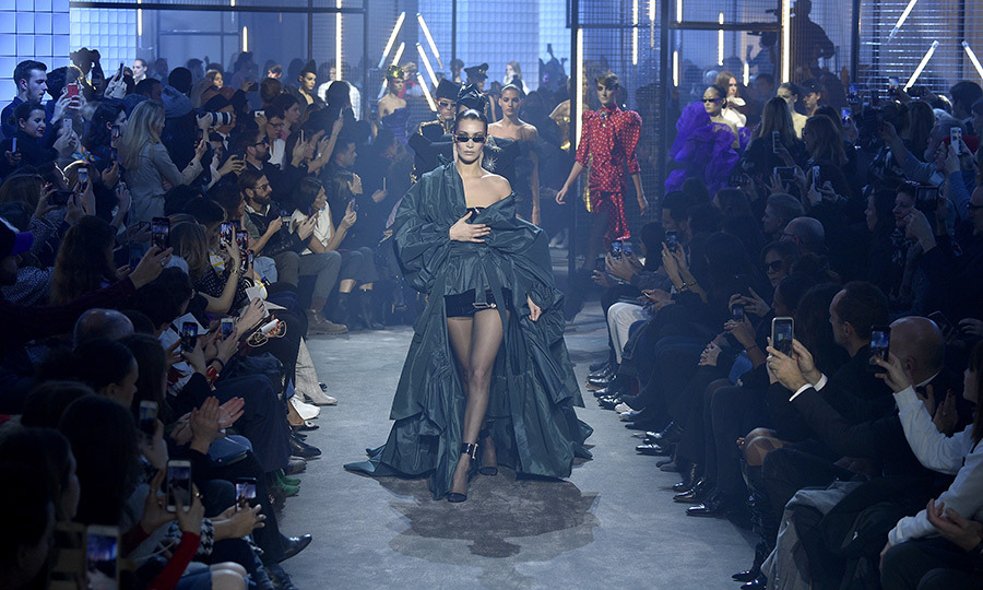 Bella Hadid, as always, was the picture of cool and fierce as she strutted down the Alexander Vauthier runway. Wearing a stunning draped emerald green getup and slick shades, the supermodel owned the club-like runway.